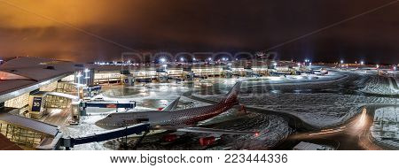 MOSCOW, RUSSIA - 25 december 2017: Night panoramic view of Terminal A of Vnukovo International Airport and airport building with teletraps and apron with airplanes