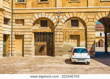 Mantova (Mantua) - July 2017, Italy: Small white car parked near the historical building of the Ducal Palace on the Square of Santa Barbara