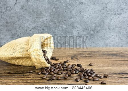 Dark brown coffee beans put in sack bags distributed on old wooden boards.