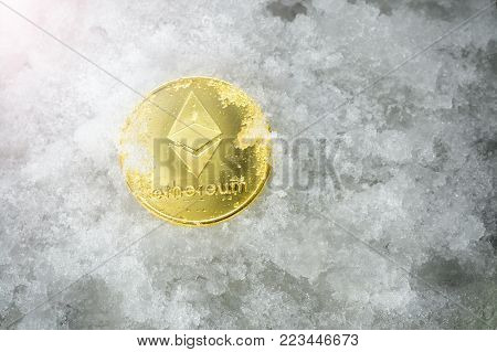 cryptocurrency physical golden ethereum (ETH) coin on snow