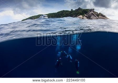 Scuba divers and tropical island. Half and half split over under photo