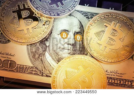 physical version of Bitcoin and Benjamin Franklin portrait with Bitcoin Eyes from one hundred american dollars; conceptual image for worldwide cryptocurrency and digital payment system