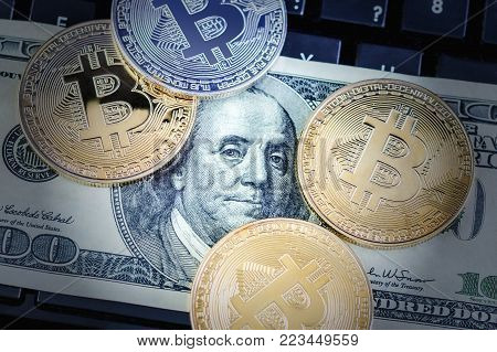 physical version of Bitcoin and Benjamin Franklin portrait from one hundred american dollars; exchange bitcoin for a dollar; conceptual image for worldwide cryptocurrency and digital payment system