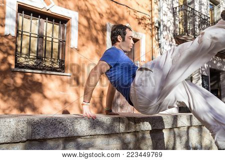 Young man doing an amazing parkour trick on the street.