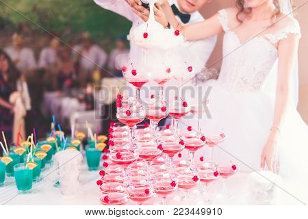Waiter serving glasses with champagne on a tray.