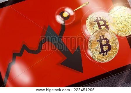Bitcoin cryptocurrency chart on tablet pc with arrow pointing down, recession. Sharp falling stock market price. Concept of economic (financial, speculative) bubble. Copyspace for text.