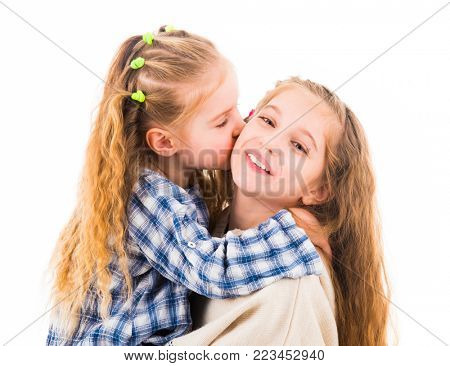 Cute little girl hugging and kissing her older sister, isolated on a white background