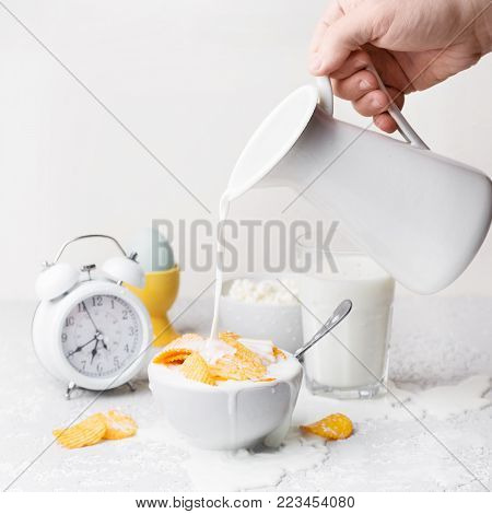 Man hand pouring milk to the white bowl with heap of golden crispy potato chips on white background, copy space. Unhealthy food concept Golden potato chips in white bowl with milk on wooden kitchen table
