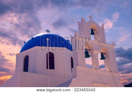 Oia Village, Santorini Cyclade islands, Greece. Beautiful view of a blue dome church at sunset.