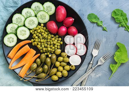 Vegetarian food. Vegetables on a plate, radish, cucumber, carrots, canned peas, pickled capers, rucola leaves.