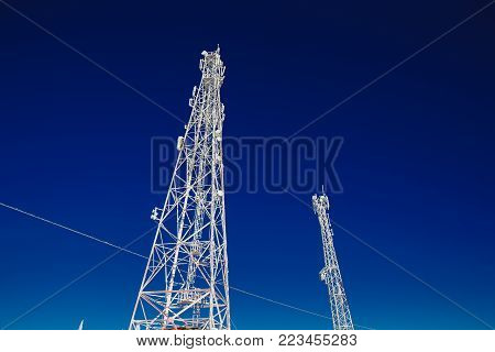 Cellular towers are icy with frost and cold, wires in the snow. abnormal frost, broken wires, winter