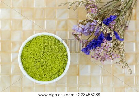 Fine Japanese Matcha green tea powder on yellow tile background, top view