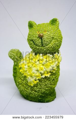 Ceramic green cat with flowers on white background