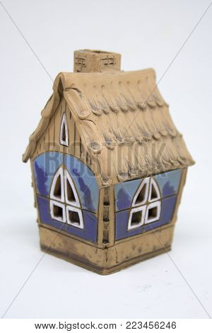 Small blue and brown ceramic house on white background