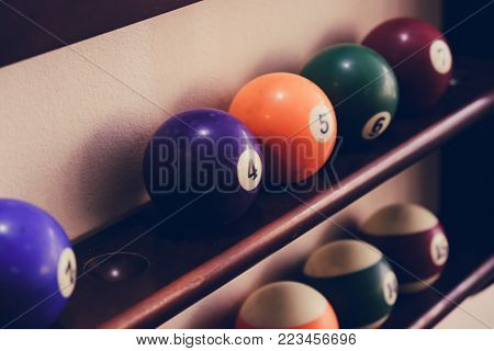Balls for pool billiards on the shelf colored or white balls for billiards on a wooden background. Close-up photo. Soft focus.