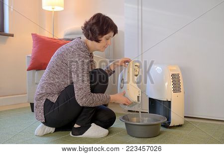Woman with Portable dehumidifier colect water, close up