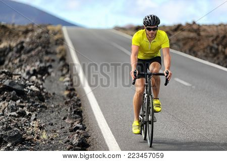 Road bike cyclist man cycling. Biking Sport fitness athlete biking on road bike. Active healthy sports lifestyle athlete cycling outside training for triathlon.