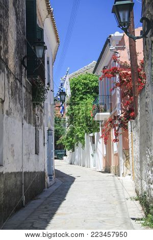 Narrow village street in Corfu, with flags and flowers. Greece