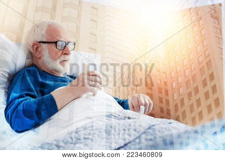 Taking medicine. Calm responsible ill pensioner looking concentrated while staying in bed and taking pills