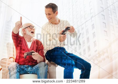 Amazing game. Excited aged man feeling happy while looking at his smiling kind son and playing video games with him