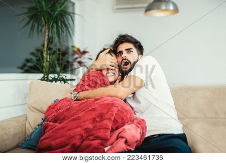 Young happy attractive couple having fun at home enjoying watching television horror movie show or thriller film covering eyes together scared in shock at home sofa