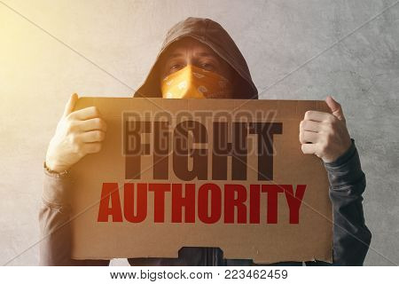 Hooded activist protestor holding Fight authority protest sign. Man with hoodie and scarf over face taking part in activism and fighting for the cause.