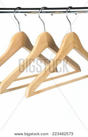 Empty wooden coat / clothes hangers on a clothes rail with a white background. Potential copy space below hangers.