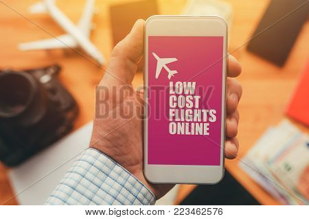 Low cost flights online mobile phone app. Man holding smartphone with mock up application screen related to holiday vacation journey trip.