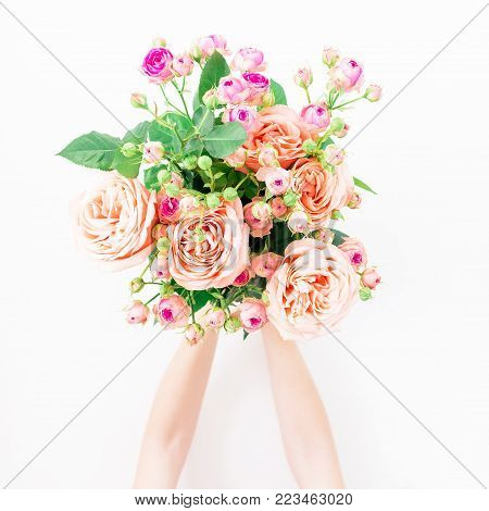 Beautiful bouquet with pink roses in girl hands isolated on white background. Flat lay, top view. Floral background