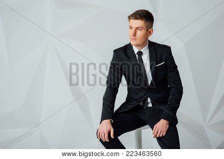 side view picture of a young business man in elegant modern suit sitting on a chair and looks away from the camera