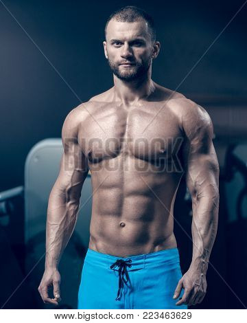 Portrait of handsome young muscular sportsman with perfect body, image with cold vintage toning