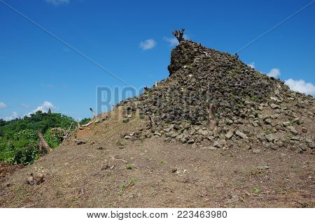 An ancient pagoda broken up into many brickson top of a hill that is being reclaimed by nature and a tree at the top of it in Mrauk U, Rakhine State, Myanmar