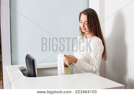 The woman-seller checks the prices for barcode