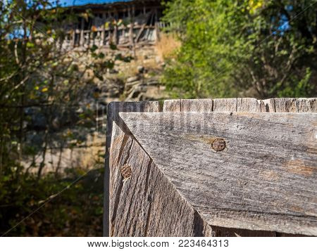 Part of an old wooden gate in the foreground, blurred old wooden barn on a rocky hill in the background, at the Fore-Balkan village of Debnevo, Bulgaria
