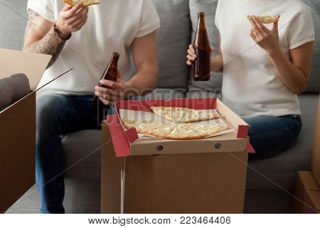 Couple eating pizza celebrating housewarming party on moving day, man and woman enjoying beer and snack sitting on sofa with unpacked boxes around, move in new home, delivery service, close up view