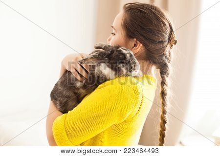 Girl holding a real Lop-eared rabbit and posing with it on camera