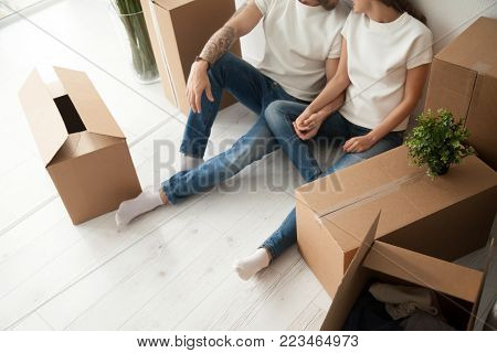 Close up view of happy couple sitting on the floor with cardboard boxes holding hands ready to relocate move in out house, young man and woman packed belongings on moving day settling in new own home