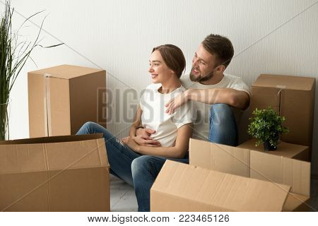 Young couple embracing looking forward to future in new home after moving in relocation, happy smiling man and woman homeowners holding hands dreaming of changes sitting on floor with boxes together