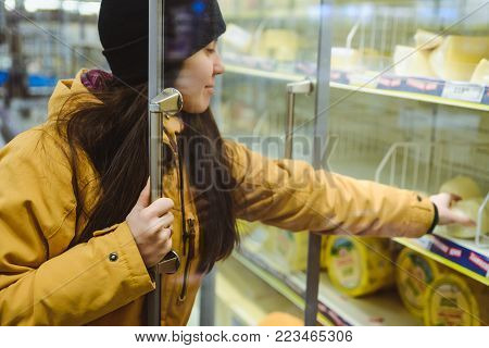 woman get cheese from the fridge in supermarket
