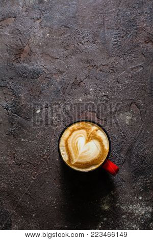 Latte art heart shape in the cup of cappuccino. Top view, vintage red cup on brown concrete textured background