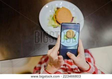 woman take picture of hamburger on her phone to share it after in socail networks