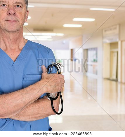 Senior doctor or medical specialist in blue scrubs and welcoming the patient to a hospital