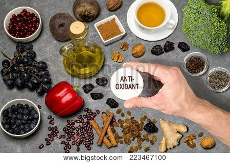 Food sources natural antioxidants. Antioxidants neutralize free radicals, have beneficial health effects. Group includes minerals, carotenoids and vitamins. Man's hand holds tag with word antioxidant