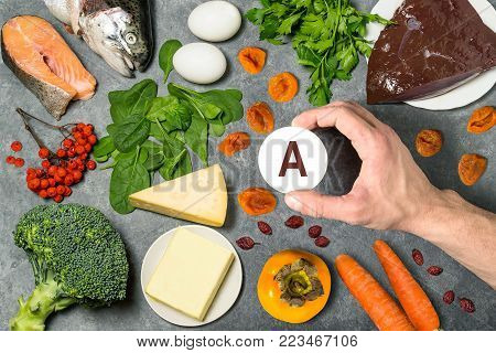 FFood rich in vitamin A. Various natural sources of vitamins. Useful food for health and balanced diet. Prevention of avitaminosis. Man's hand holds tag with name of vitamin A. Top view
