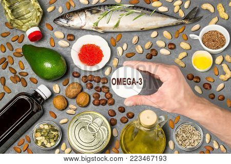 Products - source of fatty acids Omega-3. Set of natural food products rich in fatty acids Omega-3. Useful food for healthy and balanced diet. Man's hand holds tag with word Omega-3. Top view