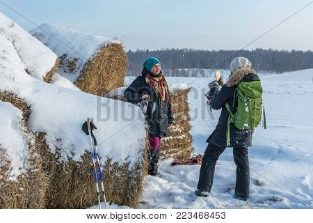 A Young Smiling Woman Is Standing Near A Haystack.