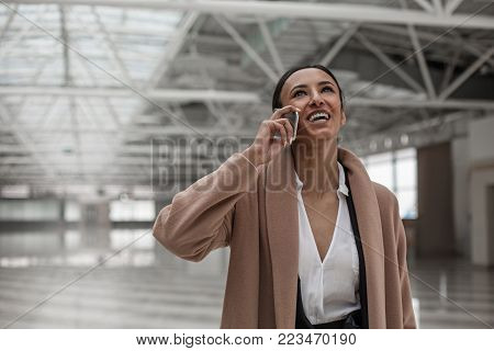 Nice to hear you. Portrait of glad stylish young woman is standing in station hall while looking up with wide smile. She is enjoying pleasant conversation on mobile phone. Copy space in the left side