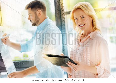 Optimistic mood. Portrait of positive professional managers using a tablet and a board while looking at you with a smile