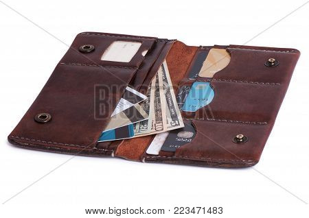 Brown leather purse with credit cards and money. On a white background.