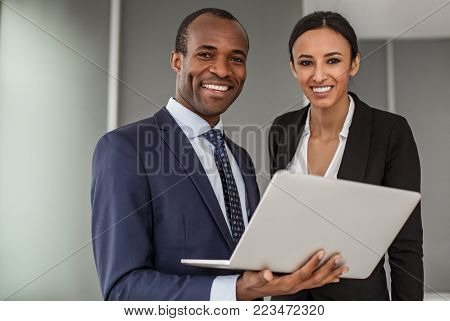 Implement new ideas. Portrait of cheerful successful young business partners wearing official clothes are standing in office. Man is keeping white laptop. They are looking at camera with joy